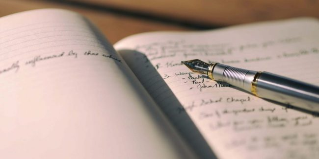 silver pen on open notebook with writing - learn English on the internet