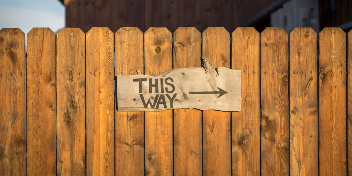 this way with arrow sign on middle of wooden fence